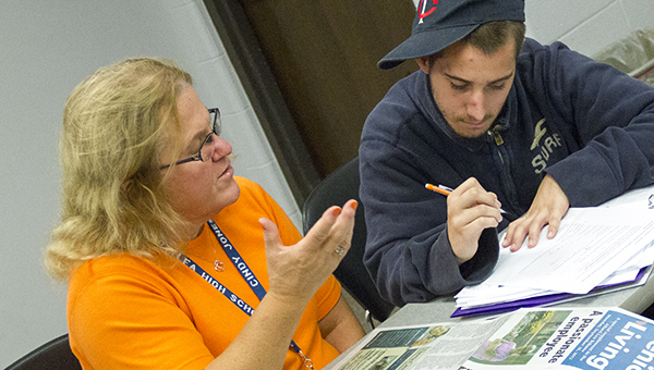 Cindy Jones helps Kenny Schultz with his work during class on Tuesday. Teacher Lori Nelson assigns work that has students read through newspapers to expand vocabulary and other lessons. --Kelli Lageson/Albert Lea Tribune