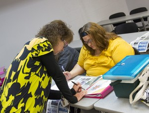 Teacher Lori Nelson helps Jessy Gulbertson during class on Tuesday.