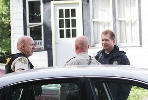 Worth County Sheriff's Office deputies talk with a Iowa Division of Criminal Investigation representative Monday at 208 Fourth St. N. in Northwood. — Sarah Stultz/Albert Lea Tribune