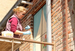 Susanne Crane, one of the organizers of the Freeborn County Arts Initiative, paints a mural over a boarded up window on the back side of Addie's Floral & Gifts Monday afternoon. -- Sarah Stultz/Albert Lea Tribune