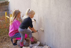Sisters Ramsey, right, and Riley Rae Shaw paint over graffiti on the back of the old Farm Bureau building on Saturday. -- Photo courtesy Julie Bronson