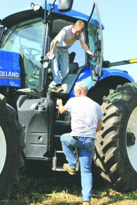 Matt Johnson of Grand Meadow, in the cab, and Mark Thorson of Rock Dell finish test driving a New Holland T8 tractor Wednesday in Lyle.