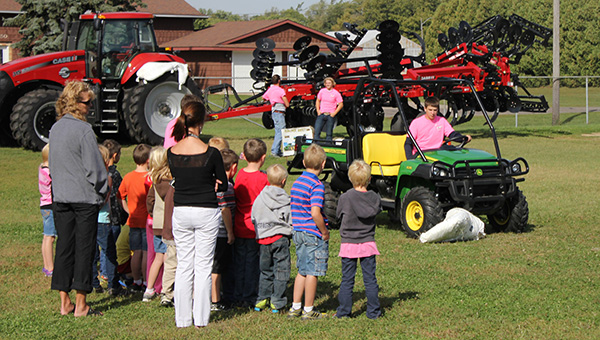 FFA member and United South Central junior Nick Krebsbach demonstrates how dangerous farm machinery can be to second graders on Tuesday. A hay dummy was caught in the equipment to show the children how quickly something can get tangled in the machine. The event was part of an all-day safety event in Wells. --Kelli Lageson/Albert Lea Tribune