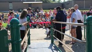 Halverson Elementary School Principal Nick Sofio cuts the ribbon to the new playground equipment Thursday. -- Tim Engstrom/Albert Lea Tribune