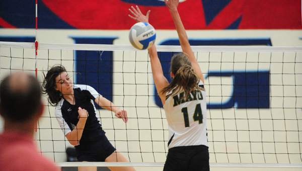 Julia Deyak of Albert Lea spikes the ball past Rochester Mayo's front Line on Friday. The Spartans won 3-0. — Micah Bader/Albert Lea Tribune