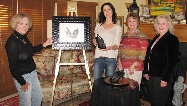 Joyce Nixon, left, stands next to a drawing of shoes created by Angie Hoffman, who is holding a shoe. Next to her is Rosalie Truax, and on the right is Barb Rognes. --Submitted