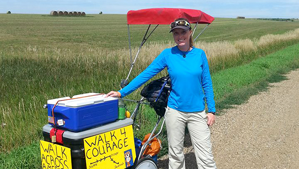 Stacie Eichinger stands with the three-wheeled cart she has been walking across America with. Eichinger's Walk 4 Courage is bringing her to Albert Lea on Saturday.  --Submitted