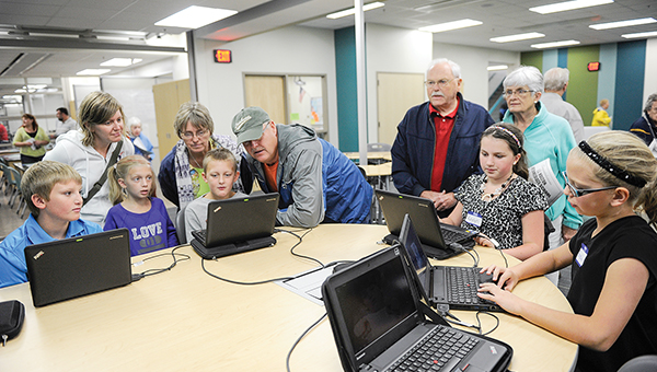 Students show off a computer workstation in one of the classrooms to people touring the I.J. Holton Intermediate School Saturday afternoon. --Eric Johnson/Albert Lea Tribune