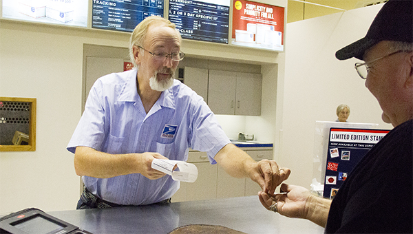 David Stewart, window clerk at the Albert Lea post office, on Wednesday gives change to Harvey Payne, of Moberly, Mo., who was mailing rabbit fur bags from the Big Island Rendezvous & Festival.  --Sarah Stultz/Albert Lea Tribune