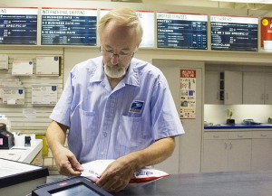 David Stewart places a mailing label on a package on Wednesday at the Albert Lea post office.