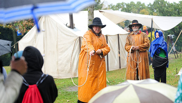 Students dressed in raincoats and holding umbrellas watch Lucy Mulholand of Oklahoma City, Okla., perform a rope trick during a school field trip to the Big Island Rendevous on Thursday.