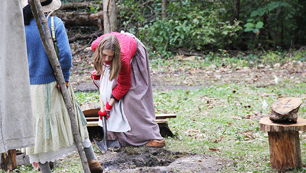 Leah Decoux, 13, watches her older sister, 14-year-old Anna, shovel dirt and ashes onto a fire Sunday afternoon at Bancroft Bay Park after the Big Island Rendezvous was over. The sisters are from Faribault and were among many vendors at the festival who took down their camps after it ended at 4 o'clock. -- Tim Engstrom/Albert Lea Tribune