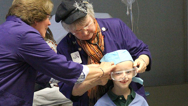 Naeve Auxiliary members Sue Tripp, left, and Jeanie Hanson help first-grader Carter James dress like a surgeon would during a tour of Mayo Clinic Health System in Albert Lea. --Kelli Lageson/Albert Lea Tribune