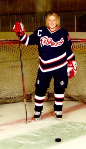 Sarah Jensen poses in front of a net at Albert Lea's City Arena during her high school playing days at Albert Lea.  The 2007 graduate of Albert Lea High School  is employed by the Los Angeles Kings of the National Hockey League. — Submitted