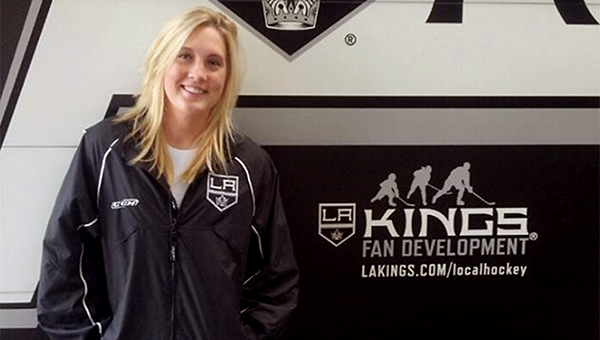Sarah Jensen stands in front of a Los Angeles Kings fan development logo. — Submitted