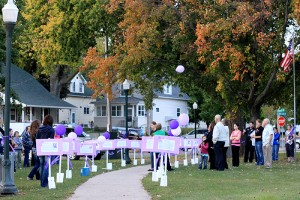 Dotti Honsey, Ilene Grosom and Albert Lea Police Department Lt. Jeff Strom spoke to more than 45 people gathered in New Denmark Park on Thursday during a vigil honoring those who have been victims of domestic violence. Signs with descriptions and photos of domestic violence victims were set up along the sidewalk with luminaries and balloons.