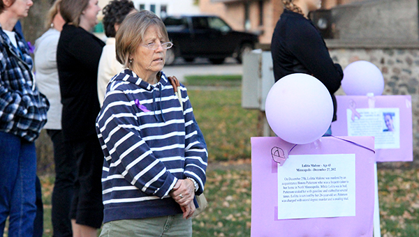 A woman reads a sign about a victim of domestic violence. Several names were read during a vigil Thursday night at New Denmark Park for domestic violence awareness. October is Domestic Violence Awareness Month. --Brandi Hagen/Albert Lea Tribune