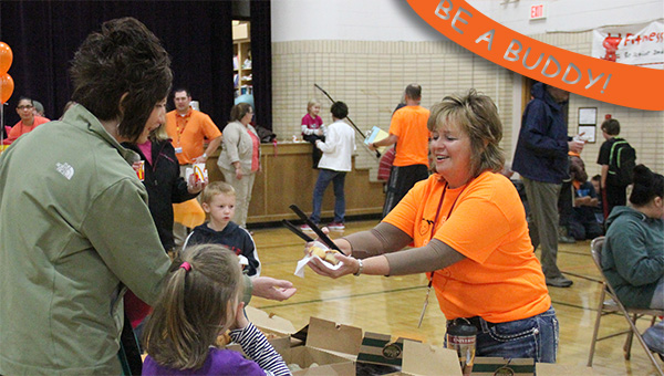 Hawthorne Elementary School teacher Michele Burkard hands out muffins to students and their guests on Tuesday during the school's Be a Buddy breakfast event. --Kelli Lageson/Albert Lea Tribune