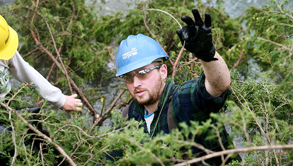 Drew Wilwert, a Conservation Corps volunteer, holds up a steel cable used to secure trees to the banks of Riceford Creek on Oct. 15 near Spring Grove. Conservation Corps workers, along with guidance from The Nature Conservancy, are using cedar trees to help stabilize the banks of Riceford Creek, which leads to the South Fork of the Root River. Waterways across Southeastern Minnesota have suffered a lot of erosion this year. -- Alex Kolyer/MPR