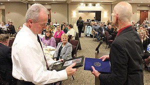 Jeff Fisher, owner of Fisher's Jewelers, inspects the plaque that declares his company to be Small Business of the Year, while Albert Lea-Freeborn County Chamber of Commerce Executive Director Randy Kehr stands at the podium Thursday at Wedgewood Cove. -- Tim Engstrom/Albert Lea Tribune