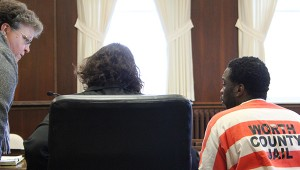 Tyrone Washington Jr. talks with his lawyers Susan Flander, left, and Nellie O'Mara during a court hearing Monday in Worth County District Court. -- Sarah Stultz/Albert Lea Tribune