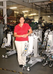 Tami LaCanne poses for a photo on the factory floor at  Lou-Rich. The device she is leaning on is made up of about 500 parts that LaCanne orders or the factory  manufactures itself.