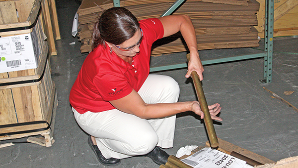 Tami LaCanne examines pipes on the factory floor at  Lou-Rich. Part of her job is to inspect shipments. --Brandi Hagen