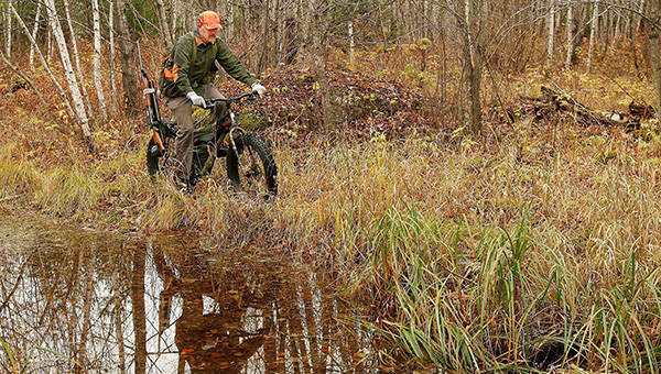 Hansi Johnson pedals a fat-tire mountain bike to a trail he wants to hunt near Duluth on Oct. 22. --Sam Cook/Duluth News Tribune