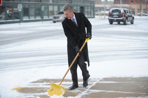 Doug Peterson of the Peterson-Savelkoul-Haedt and Benda law office scoops snow off the sidewalk this morning. -- Micah Bader/Albert Lea Tribune