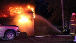 Firefighters begin dousing the flames with a hose Monday morning. The nearest hydrants were by Walgreens across the street. -- Tim Engstrom/Albert Lea Tribune