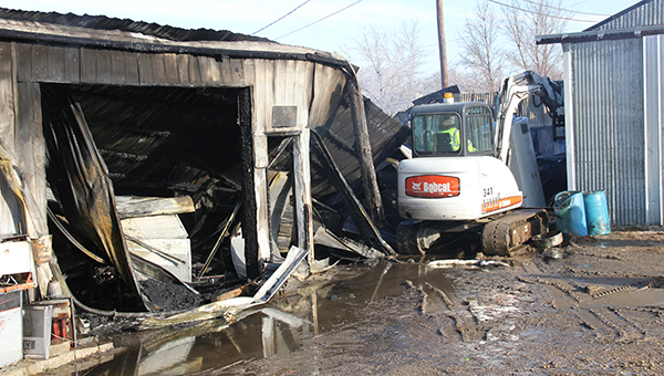 A firefighter operates a skidloader Monday morning to knock down walls at a shed behind Subway on East Main Street near the Union Pacific Railroad tracks.