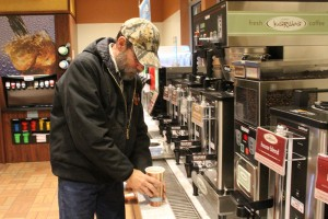 Rodger Mathans of Conger fills a cup of coffee this morning at the new Kwik Trip on Bridge Avenue. The store opened at 5 a.m., in time for the long Thanksgiving weekend.