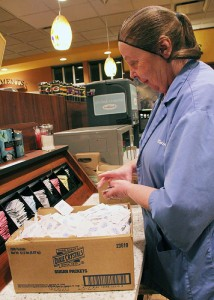 Kwik Trip employee Dawn Miller loads sugar and sweetener packets in the new store on Bridge Avenue.