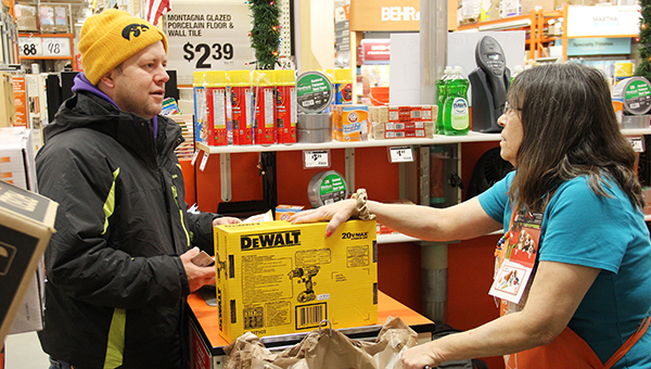 Matt Otten of Mason City checks out this morning with the help of cashier Beth Cole at the Albert Lea Home Depot. The store opened at 5 a.m. instead of opening on Thanksgiving night to give its employees time to spend with their families. --Sarah Stultz/Albert Lea Tribune