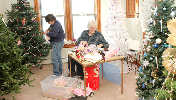 Ann Crowley, left, and Karen Callahan decorate a doll tree in a room in the upstairs of the Historic Petran House. --Brandi Hagen/Albert Lea Tribune