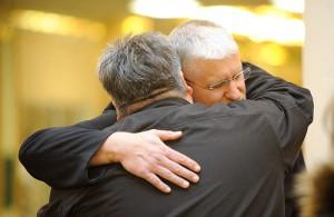 The Rev. George Marin of Grace Christian Church hugs Capt. Jim Brickson as he says a prayer at the start of Brickson's world record attempt. -- Brandi Hagen/Albert Lea Tribune