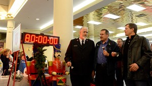 Capt. Jim Brickson of the Albert Lea Salvation Army stands with former mayor Mike Murtaugh, who is chairman of the Salvation Army advisory board, and current mayor Vern Rasmussen as the world record for bell ringing of 80 hours appears on the time clock. -- Brandi Hagen/Albert Lea Tribune
