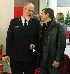 The red glow of a digital clock shines on the faces of Salvation Army Capt. Jim Brickson and Albert Lea Mayor Vern Rasmussen as they talk Friday while ringing bells. -- Tim Engstrom/Albert Lea Tribune