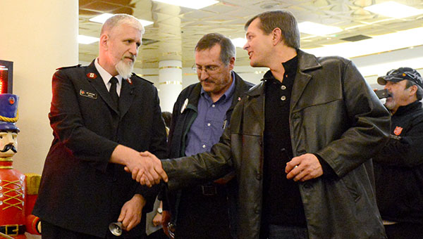 Salvation Army Capt. Jim Brickson, left, shakes hands with Albert Lea Mayor Vern Rasmussen on Friday night after breaking the world record of 80 hours ringing a Salvation Army bell. At center is Mike Murtaugh. --Brandi Hagen/Albert Lea Tribune