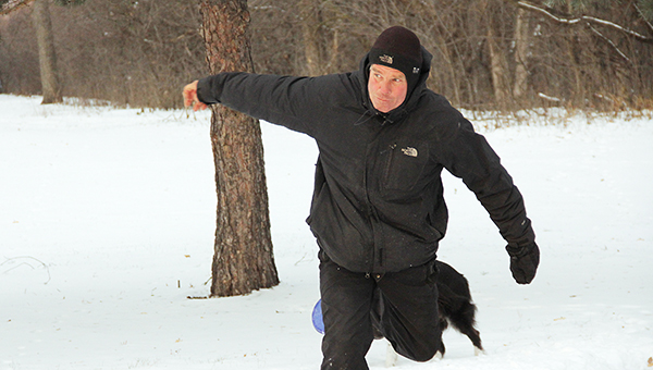 Dave Sime tees off at Hole 6 of Oak Island Disc Golf Course at Bancroft Bay Park on Friday. He brings his dog, Spirit, with him when he plays. The dog likes to fetch its disc, but not the ones Sime throws. -- Tim Engstrom/Albert Lea Tribune