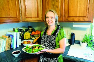 """Anne Hoelz of Albert Lea stands in her kitchen with some of the recipes she has created for her cookbook """"Cavemom's Cooking."""""""