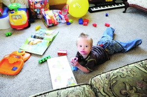 Kaiden Hoelz plays with books and toys on the floor of his home.