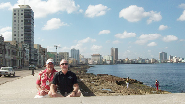 Larry Alvey, left, and David Nelson of 4-Seasons Vacations in Albert Lea sit on a seawall in Havana, Cuba, called the Malecón. It stretches for eight kilometers. — Submitted