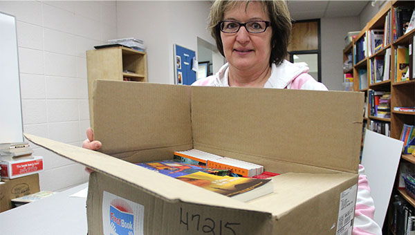Mary Jo Doorman, literacy specialist for the Albert Lea district, holds one of the boxes of books from First Book. --Tiffany Krupke/Albert Lea Tribune
