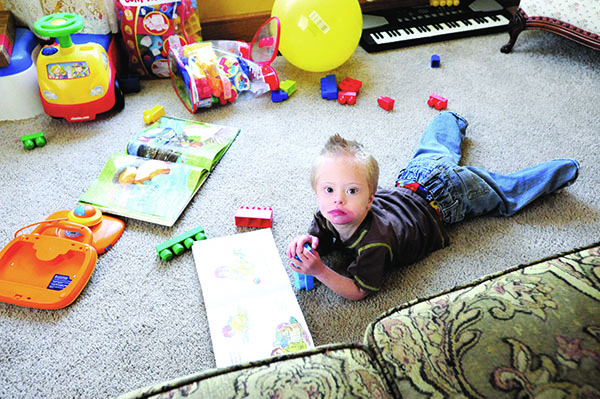 Kaiden Hoelz plays with books and toys on the floor of his home. He has Down syndrome and autism, and a new computer device is helping him learn to communicate. --Brandi Hagen/Albert Lea Tribune