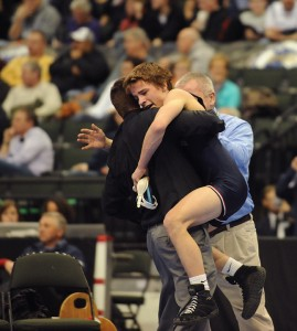 Garrett Aldrich of Albert Lea celebrates with assistant coach Brian Goodnature on March 1 after he won the Class AA championship match at 106 pounds at the Xcel Center in St. Paul. – Micah Bader/Albert Lea Tribune