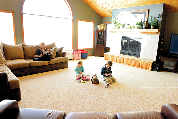 This family space is easily shared by Nicole, Kade, Grant and Gabriel. Toy bins keep the toys contained, a baby crib with cupboard doors doubles as storage and by having the couch pulled away from the wall, toys can be kept out of sight. – Brandi Hagen/Albert Lea Tribune