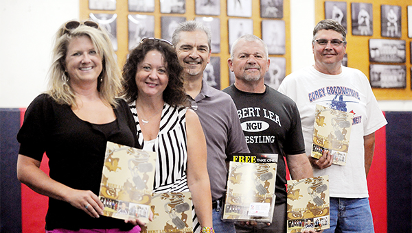 A magazine chronicling the history of the Albert Lea wrestling program was published as a group effort of the Albert Lea wrestling booster club, Youth 1st and Church Offset Printing Inc. From left are Ann Glazier, secretary of the booster club; Kim Christianson, page designer from Church Offset Printing; Mark Arjes, director of Youth 1st; and Brad Nelson, president of the booster club. — Micah Bader/Albert Lea Tribune