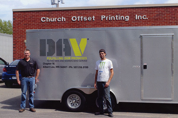 The new Disabled American Veterans trailer has new signage thanks to Mike Kruse, Church Offset Printing and the installation skills of Nick Kruse, left. Pictured right is Cody Hoenisch. A portion of the cost of the trailer was donated to DAV by Florrie Clausen. The trailer is used to transport clothing and other small household items that have been dropped in DAV containers. Containers are in the south parking lot next to Herberger's, at the Freeborn Coop. across from St. Theodores, in front of Market Place grocery, at the bank in Alden and at the Aemrican Legion in Freeborn. – Provided