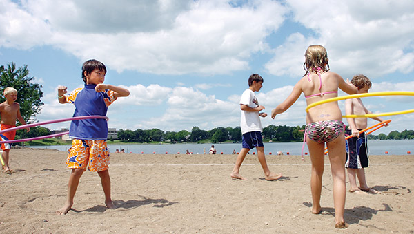 Children play with hula hoops a few years ago during a luau at the City Beach organized by the Albert Lea Parks and Recreation Department. – Brie Cohen/Albert Lea Tribune